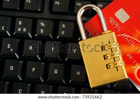 Shopping on-line concept with a credit-card and padlock over a computer keyboard - stock photo
