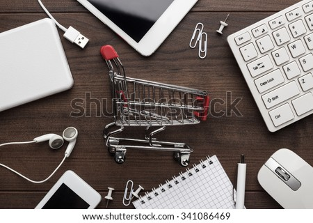 shopping online concept. small red trolley and gadgets on the table - stock photo
