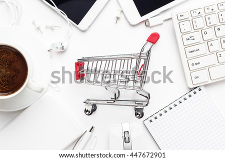 shopping online concept. small red trolley, different gadgets and stationery on the white office table - stock photo
