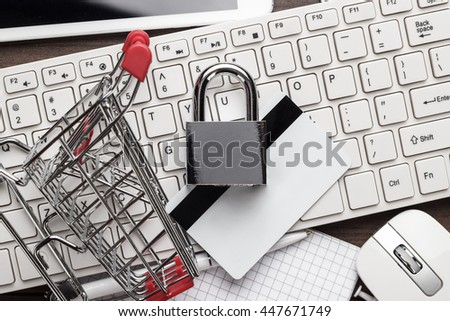 shopping online safely concept. small red trolley, padlock, credit card and computer on the table - stock photo