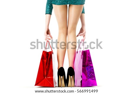 Shopping, sale and holiday concept - elegant woman in brilliant green dress with shopping red bags. Sexy girl on gold heels picks. Young girl in black shoes goes on sale in the mall. Back view