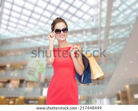 shopping, sale, christmas and holiday concept - smiling elegant woman in red dress and sunglasses with shopping bags - stock photo