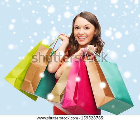 shopping, sale, gifts, christmas, x-mas concept - smiling woman in red dress with shopping bags - stock photo