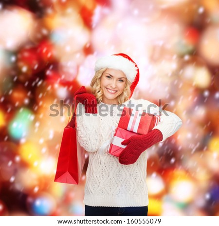 shopping, sale, gifts, christmas, x-mas concept - smiling woman in santa helper hat with shopping bags and gift boxes - stock photo