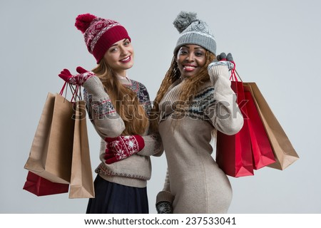 Shopping, sale, gifts, christmas, xmas concept - two smiling women in knitted dress with shopping bags - stock photo