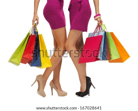 shopping, sale, gifts concept - two women in pink dresses with shopping bags - stock photo