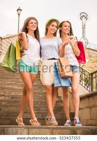 shopping, sale, happy people and tourism concept - three beautiful girls in sunglasses with shopping bags in city - stock photo
