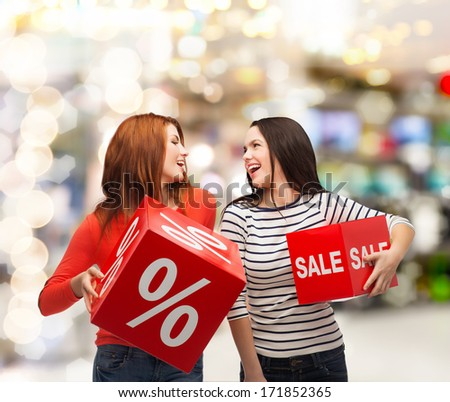 shopping, sale, mall and gift sconcept - two smiling teenage girls with percent and sale sign on red box at shopping mall
