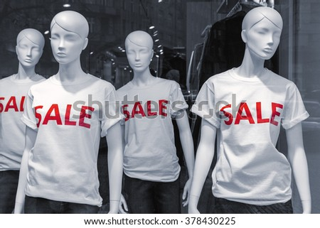 Shopping sale window display with four mannequins wearing t-shirts with text Sale  - stock photo
