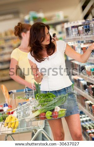 Shopping series - Beautiful brunette in a supermarket and holding shopping basket - stock photo