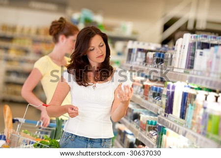 Shopping series - Brown hair woman in cosmetics department holding bottle of shampoo - stock photo