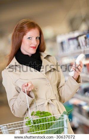 Shopping series - Red hair woman buying shampoo in a supermarket - stock photo