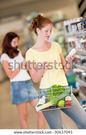 Shopping series - Red hair woman in cosmetics department choosing shampoo - stock photo