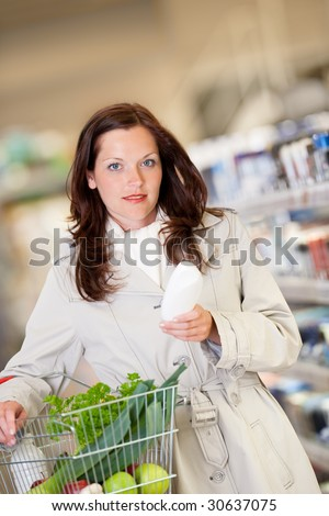 Shopping series - Young woman buying shampoo and holding shopping basket - stock photo