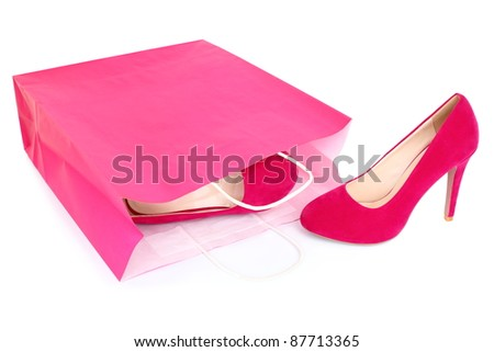 Shopping shoes isolated. Red / pink high heels shoes and shopping bag closeup isolated on white background.