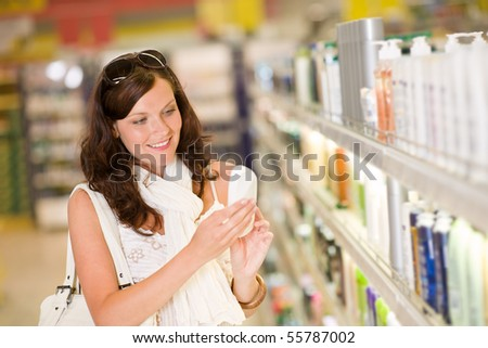 Shopping - smiling woman with bottle of shampoo in supermarket - stock photo