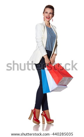 Shopping. The French way. Full length portrait of excited young woman with French flag colours shopping bags on white background looking on copy space