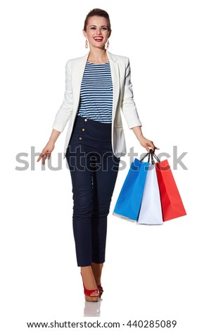 Shopping. The French way. Full length portrait of happy young woman with French flag colours shopping bags on white background going forward - stock photo