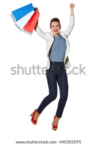 Shopping. The French way. Full length portrait of happy young woman with French flag colours shopping bags jumping against white background - stock photo