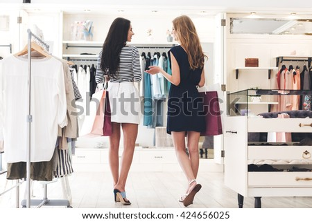 Shopping therapy in action. Rear view of two beautiful women with shopping bags looking at each other with smile while walking at the clothing store - stock photo