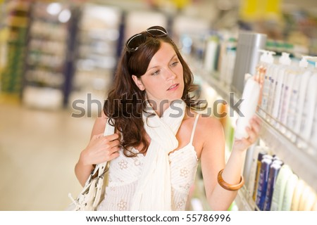 Shopping - thoughtful woman looking at bottle of shampoo in supermarket - stock photo