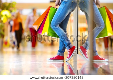 Shopping time, closeup of teenage girl's legs with shopping bags at shopping mall - stock photo