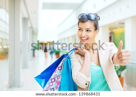 Shopping time, woman at mall showing thumbs up