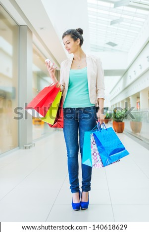 Shopping time, woman at mall with smartphone - stock photo