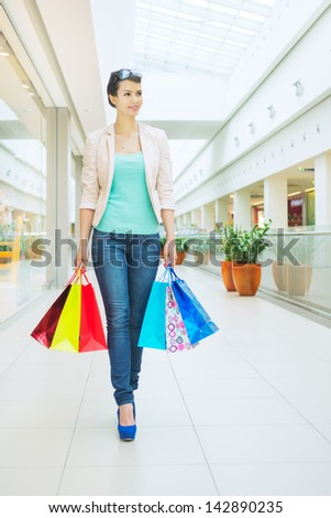 Shopping time Young woman at mall, with bags, looking away, smiling - stock photo
