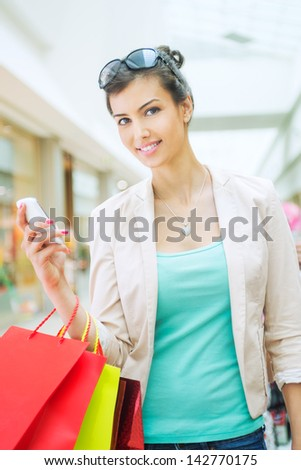 Shopping time Young woman with shopping bags, using smart phone at mall - stock photo