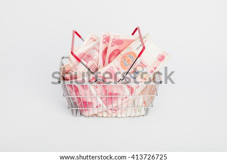 Shopping trolley basket or cart of Yuan - currency. Symbolic example of spending money in shops, or advantageous purchase in the shopping center. Yuan notes from China's currency. Chinese banknotes - stock photo