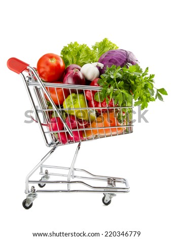 Shopping trolley full of fresh vegetables isolated on a white background - stock photo