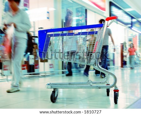 Shopping Trolley In A Mall With Moving People In The Background - stock photo
