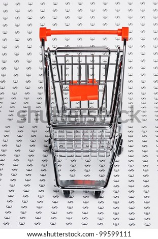 shopping trolley on the background of the icons of money - stock photo