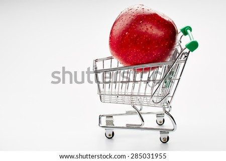 Shopping trolley with apple with text space  - stock photo
