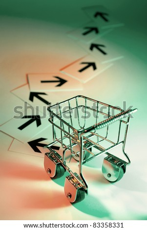 Shopping Trolley with Arrows with Green Background - stock photo