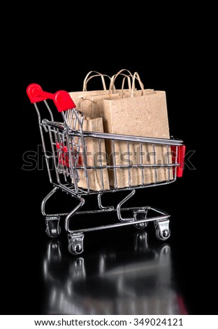 shopping trolley with eco paper bags is isolated on black background - stock photo