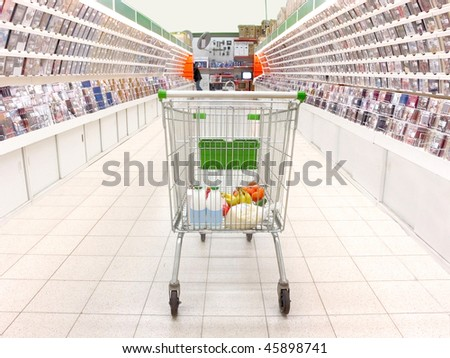 shopping trolley with purchases in the supermarket. Focus is under the back site of trolley - stock photo