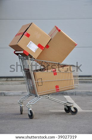 Shopping wheal loaded with packets - stock photo