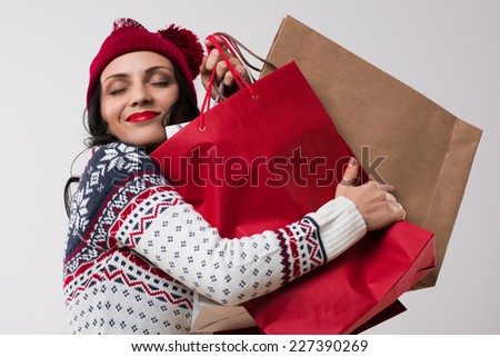 Shopping winter woman embracing shopping bags with eyes closed on white background.  - stock photo