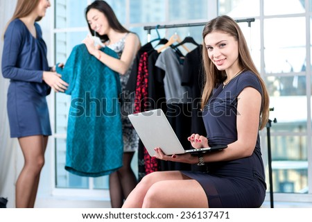 Shopping with best friends. Smiling girl doing internet shopping in the laptop and  looking at the camera while her friend choose the dress on a hanger. Girls having fun together doing shopping