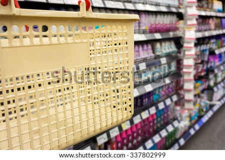 Shopping with cream plastic basket. Browsing the available goods in supermarket. - stock photo