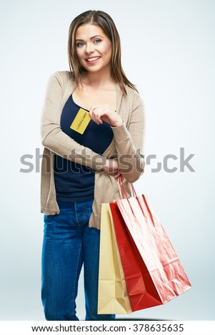 Shopping with credit card. Happy woman hold shopping bag. Studio isolated portrait.