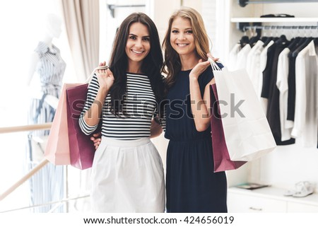 Shopping with friend is pure pleasure! Two beautiful women with shopping bags looking at camera with smile while standing at the clothing store - stock photo