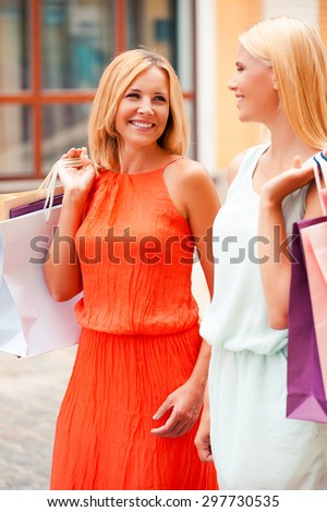Shopping with her best friend. Cheerful mother and her daughter carrying shopping bags and looking at each other while walking outdoors - stock photo