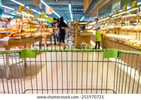 Shopping with shopping cart in bakery department of supermarket - stock photo