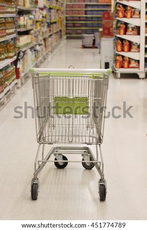 Shopping with shopping cart in snack department of supermarket - stock photo
