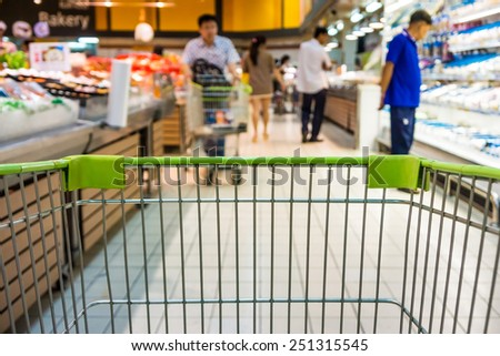 Shopping with shopping cart in supermarket - stock photo
