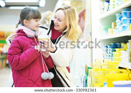 Shopping. woman and girl choosing dairy products in shop supermarket - stock photo