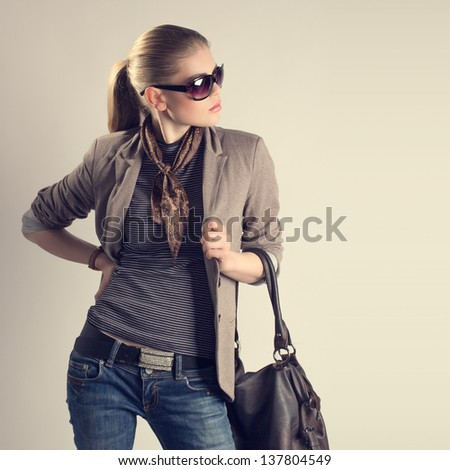 Shopping woman. Attractive young Caucasian fashion girl in sunglasses holding a leather bag and looking aside. - stock photo
